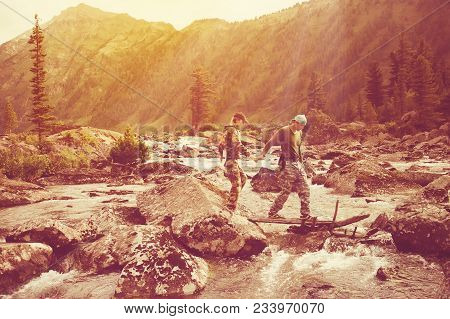 Tourists Guy And Girl Go Over The Mountain River Holding Hands. Walk In Nature. Hikers Make Their Wa