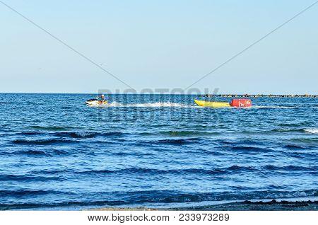Mamaia, Romania - September 15, 2017: Man Riding A Jet Ski Over Blue Black Sea Water, Banana Boat