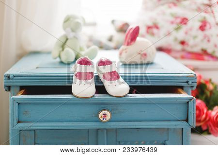 Cute Leather Booties For Little Girl. White Accessory For Girl Outfit. Tiny Shoes On Wooden Backgrou