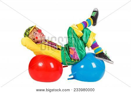Funny Clown Lies On Balls Isolated On White Background