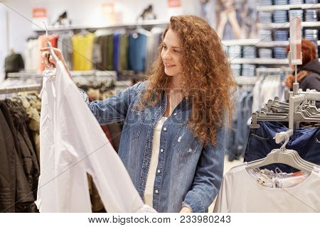 Photo Of Pleased Female Shopaholic Chooses Clothes For Party, Holds Shirt On Hangers, Going To Buy N
