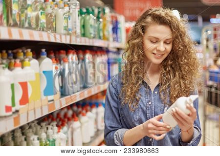 Young Housewife With Pretty Attractive Look, Chooses Household Products Or Detergent For Cleaning Ho