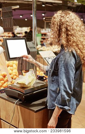 Vertical Shot Of Young Woman Weighs Bananas On Electronic Scales With Touch Screen, Buys Fruits In S