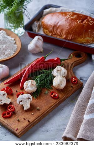 Countryside Cuisine Still Life With Tasty Homemade Pie, Fresh Mushrooms, Hot Pepper, Garlic And Herb