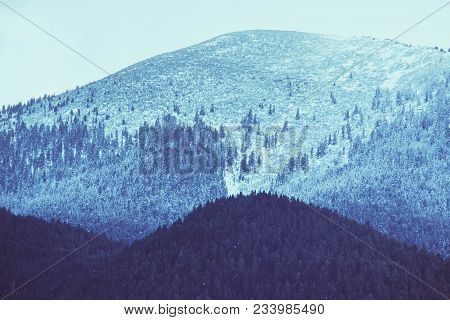 Photo depicting a beautiful moody frosty landscape European alpine mountains with snow peaks on a blue sky background. poster