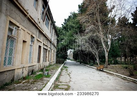 Abandoned Village House Building In Baku Botanical Garden. Nobody In The Park With Trees. Springtime