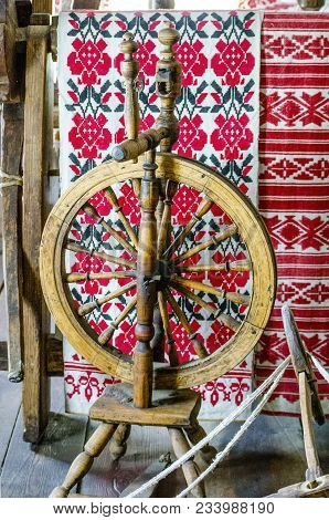 Ancient Wooden Spinning Wheel On The Background Of A Ethnic Patterns