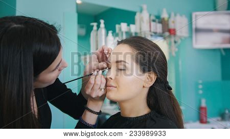 Makeup Artist And Hairdresser Working With Client In The Beauty Shop, Fashion And Beauty Concept