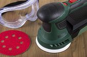 Orbital power sander with safety goggles and sanding disc on a wooden workbench poster