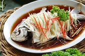 Chinese food, whole steamed fish in soy sauce on the dish poster