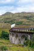 Jacobite Steam Train Locomotive passing Glenfinnan Viaduct, the famous location appears on the films poster