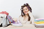 Young pretty housewife with curlers on hair in light clothes ironing family clothing on ironing board with iron. Woman isolated on white background. Housekeeping concept. Copy space for advertisement poster