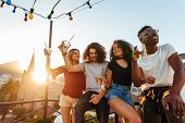 Group of young friends having fun, drinking and enjoying a evening on rooftop. Multiracial men and woman hanging out at rooftop party in evening. poster