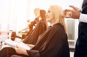 Female stylist combs blond straight hair of mature woman in beauty salon. Mature pretty woman is doing hairdo in beauty salon. poster