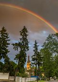 Rainbow above old Lutheran church in Dubulti, Jurmala, Latvia. The church was built in 1909 with traits of asymmetry and national Latvian romanticism style.  poster