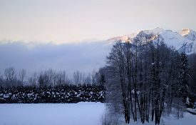 In This Winter Landscape, Morning Fog Rises Above The Schmittenhöhe And Kitzsteinhorn Mountains In T
