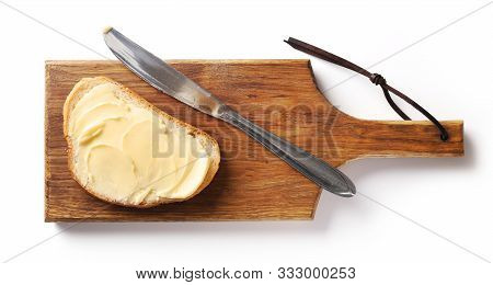 Bread With Butter On Wooden Cutting Board, Top View