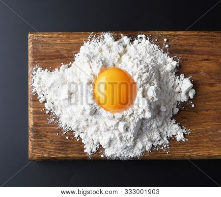 Flour And Egg Yolk On Wooden Cutting Board, Top View