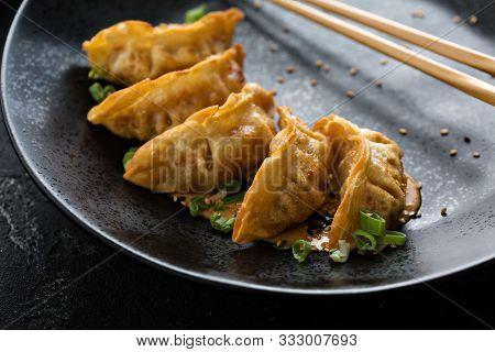Fried Potstickers Or Dumplings On A Black Plate