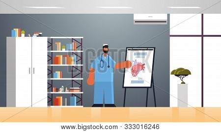 Male Doctor Cardiologist In Uniform Presenting Flip Chart With Human Heart Medicine Healthcare Conce