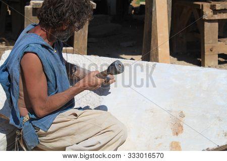 Sculptor Working A Block Of Stone With A Chisel In Guedelon Chateau, Treigny, France Guedelon Chatea