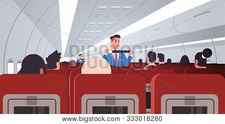 Steward Explaining For Passengers How To Use Seat Belt Fastening In Emergency Situation Male Flight