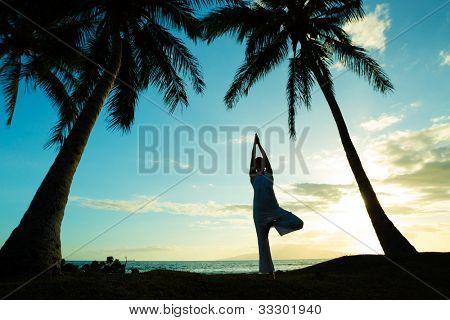 Woman doing Yoga bei Sonnenuntergang
