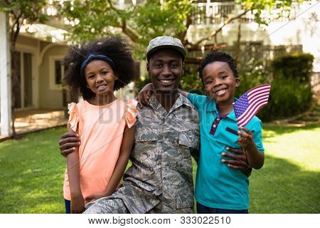 Portrait of a young adult African American male soldier in the garden outside his home, kneeling with his arms around his young son and daughter, all of them smiling to camera, his son holding a US poster