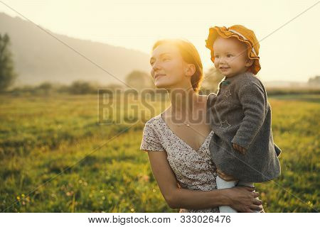Young Mother And Baby Girl In Sunlight At Sunset On Nature Outdoors. Mother And Child In Meadow In E