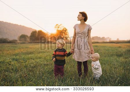 Young Mother With Children In Sunlight At Sunset On Nature Outdoors. Parents And Kids In Meadow In E