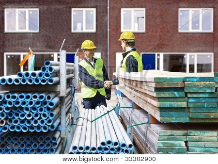 Two building contractors shaking hands behind stacks of scaffolding material, in front of a newly completed residential building complex