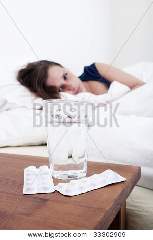 Glass of water and two strips of pain killers on the bed side table with a young, sick, woman in the background