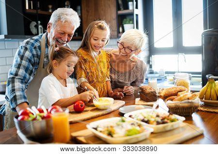 Happy Senior Couple Having Breakfast With Their Grandchildren At Home