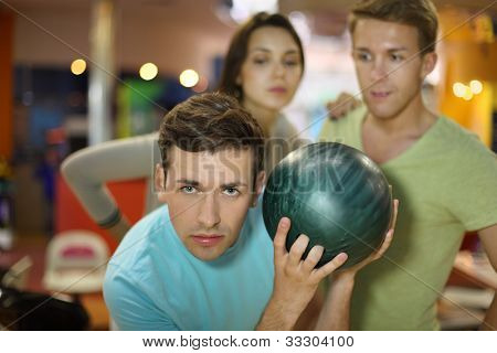 Young man prepares to throw of ball in bowling; man and woman look at him; focus on left man; shallow depth of field