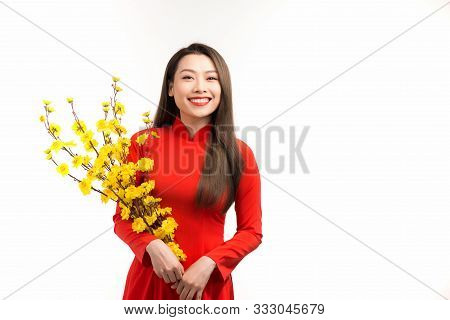Portrait of a beautiful Asian girl in ao dai with yellow flower apricot on traditional festival poster