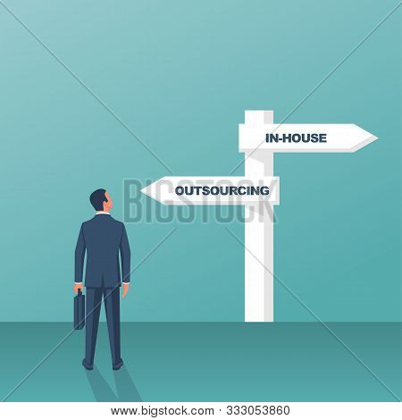 Outsource Or Inhouse - Signpost. Businessman In Front Of A Road Sign. The Choice Of Man. Banner Outs