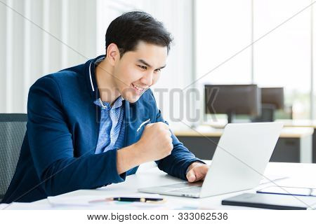 Happy Of Asian Young Businessman See A Successful Business Plan On The Laptop Computer And Pen On Wo