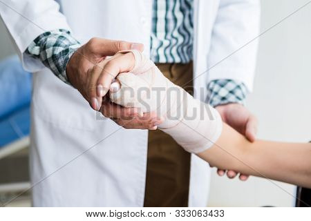 Close-up Of Man Doctor Of Checking Splint The Arm Of Female Patient Hand Due To With Her Arm Broken
