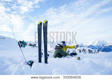 Picture of skis, ski poles against background of two sports women with thermos sitting in ski resort in winter.