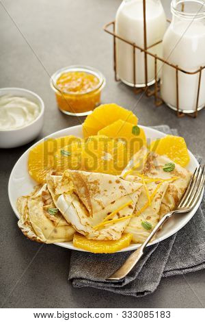 Thin Crepes Suzette With Orange Slices And Marmalade For Breakfast