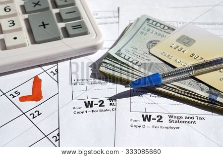 W-2 Wage And Tax Statement Blank With Credit Card On Dollar Bills, Calculator And Pen On Calendar Pa