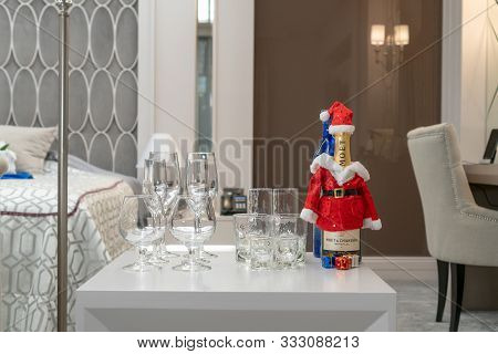 Bottle Of Moet Chandon Champagne In Santa Claus Hat And Glasses On The Table In A Luxurious Hotel Ro