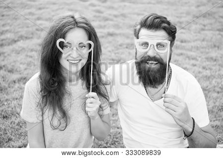 Fun Valentines Props. Bearded Man And Sexy Girl Smiling With Fancy Party Props On Green Grass. Funny