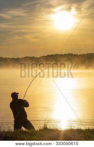 Angler Catching The Fish During Hazy Summer Sunrise