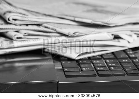 Pile Of Newspapers On A Laptop Close-up. World News Concept