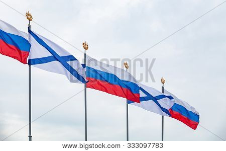 Ensigns of the Russian Navy and Flags of Russia are waving on wind under blue cloudy sky. Military parade decoration, Saint-Petersburg, Russia poster