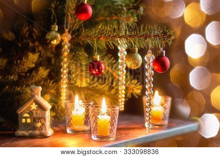 Burning Candles On Wooden Table Under Christmas Tree Decorated With Christmas Toys With Bokeh Lights