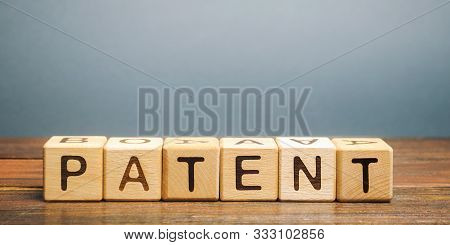 Wooden Blocks With The Word Patent. Form Of Intellectual Property. Document Attesting The Right Of A