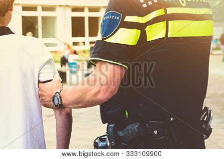 Policeman arresting young boy on schoolyard. Holding teenager at his arm