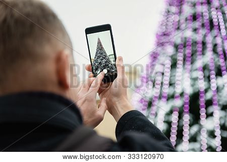 Man Is Taking Pictures With A Smartphone On The Christmas Tree.
